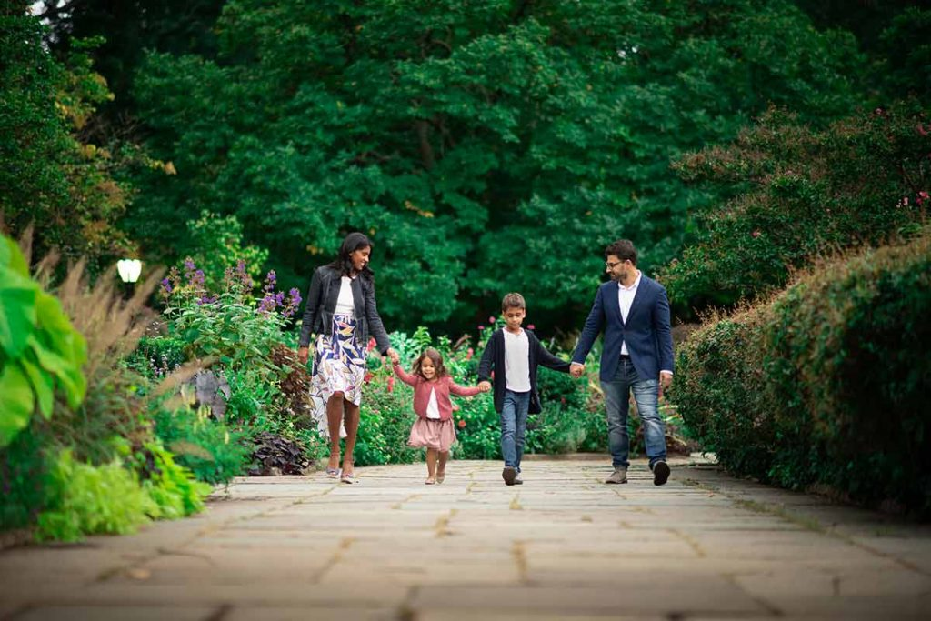 A modern NYC family walks along a path in NYC's Central Park