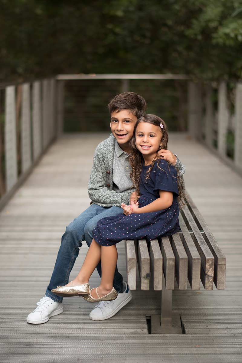 A brother and his little sister smiling on NYC's Highline Park