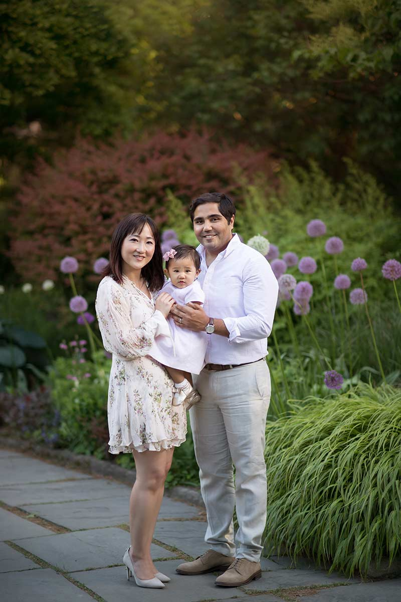 A happy mother and father holding their daughter in the botanical gardens NYC