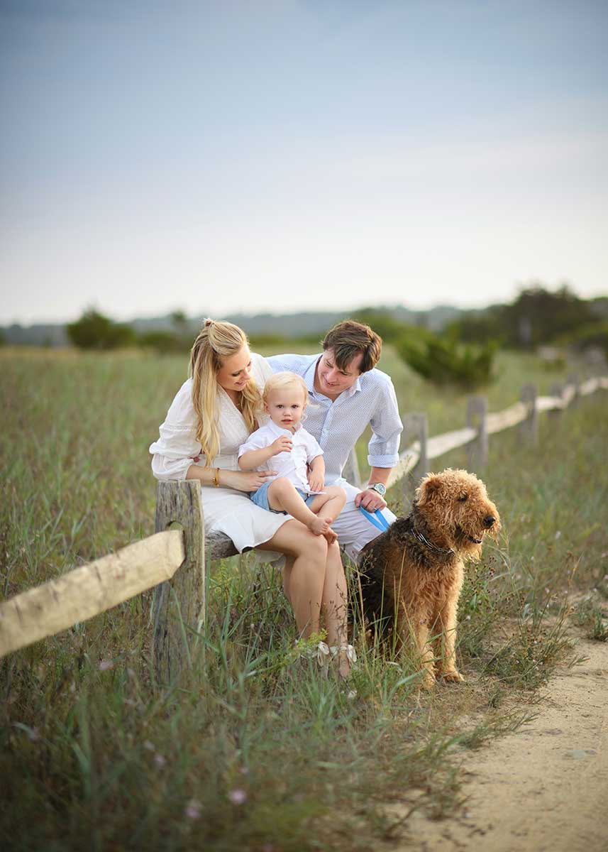 A family from the Hamptons sitting on a farm fence along with their baby and family pet