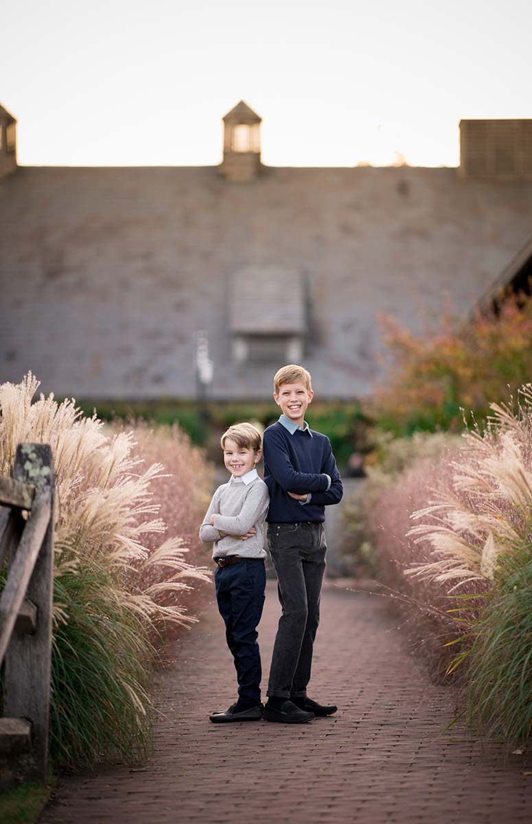 Two brothers standing on a brick path at a farm in Westchester County NY
