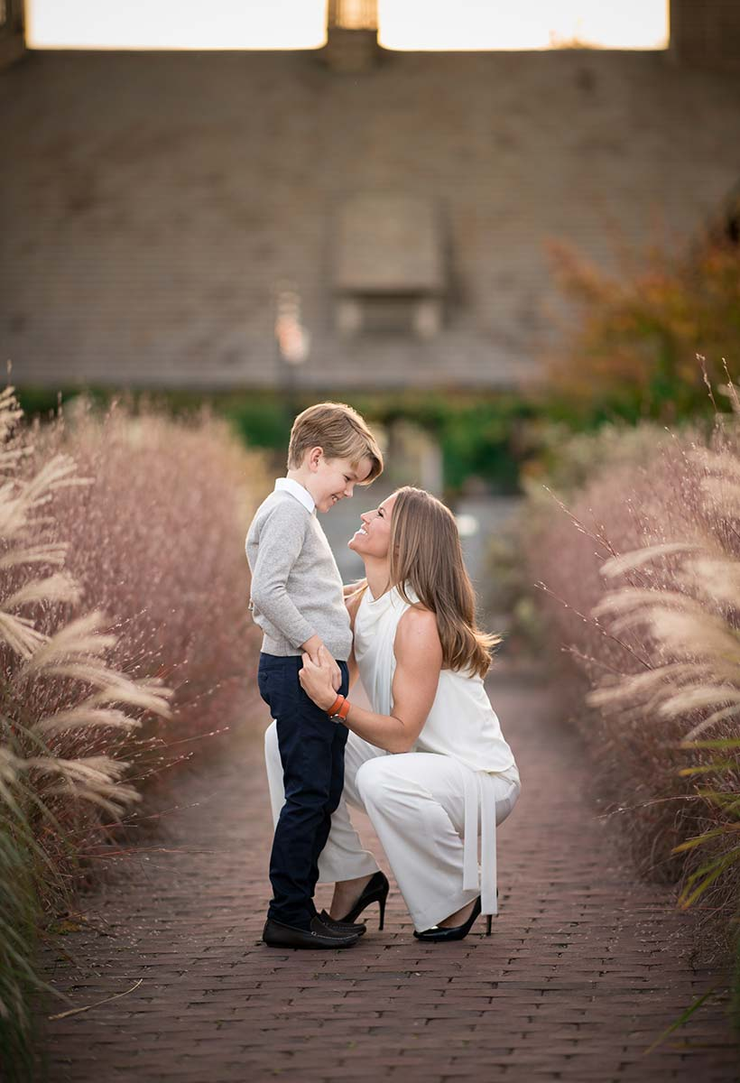 Happy mother holding the hands of her son on a brick path at a farm in Westchester County NY