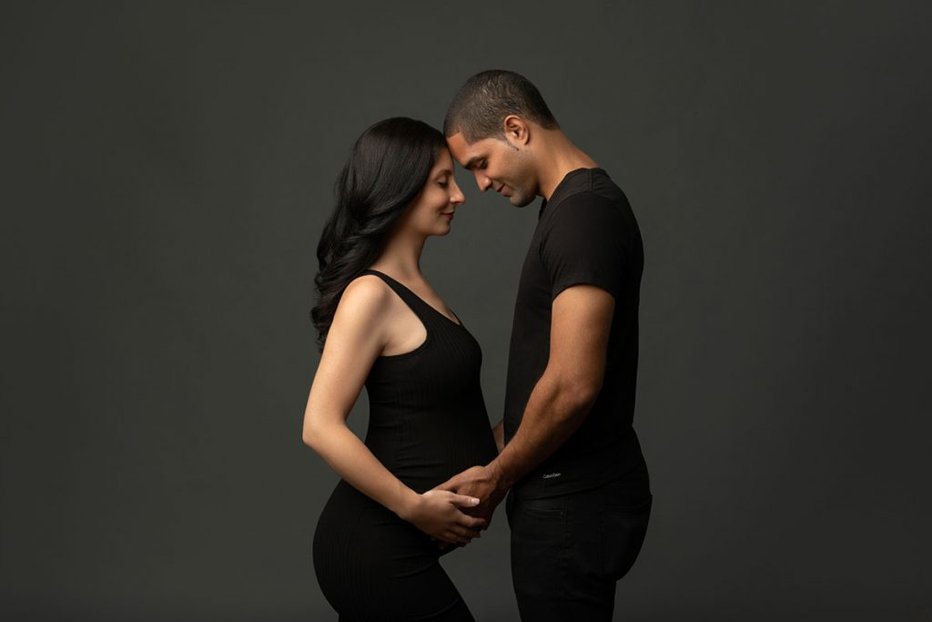 Pregnant couple holding hands and smiling happily