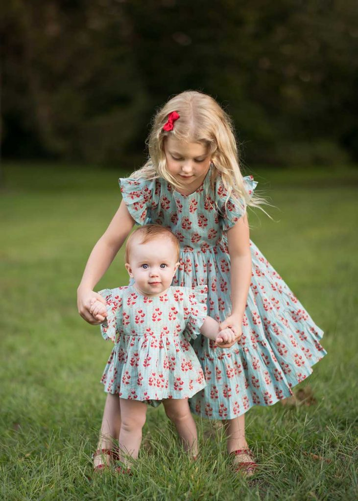 Two little sisters in matching dresses holding hands in NYC's Central Park