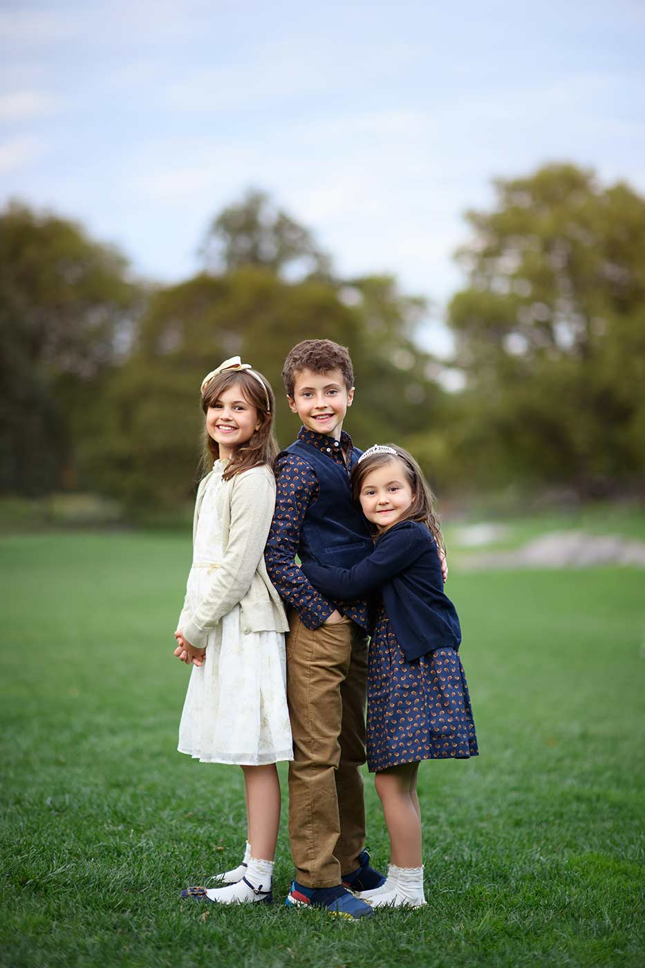 Brother and his sisters posing for a photo in Central Park's meadow