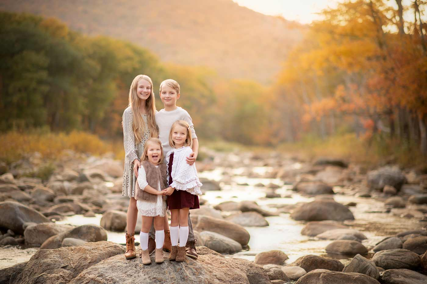 Siblings standing near a river during autumn sunset