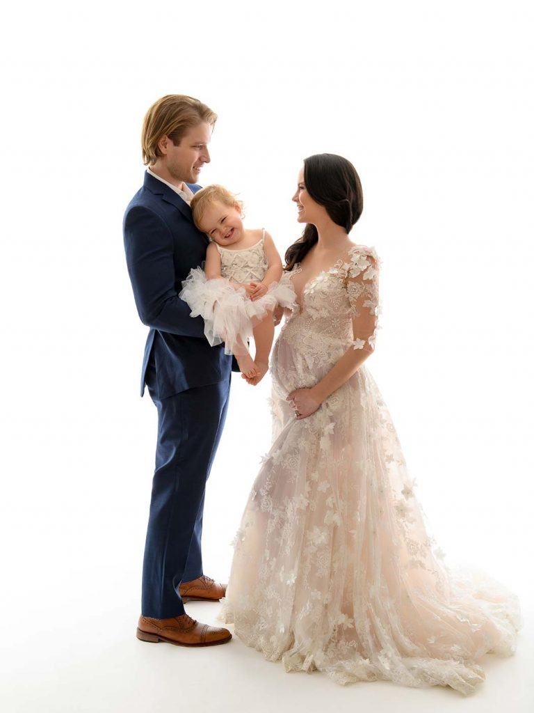 formal family portrait of pegnant mother in lace gown with husband and baby