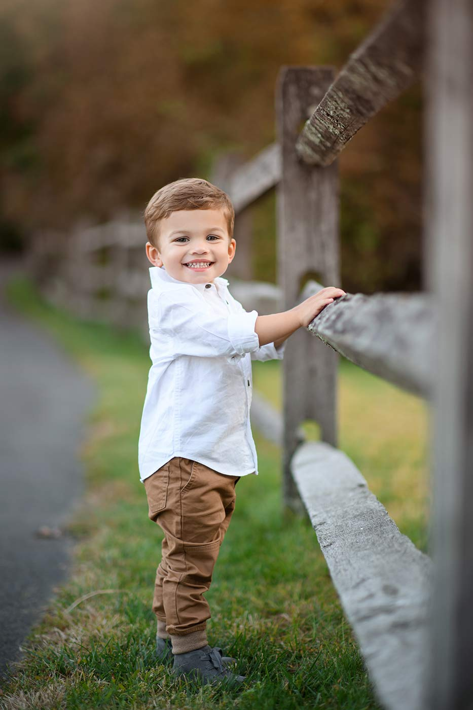 Wooden farm fence with a handsome toddler