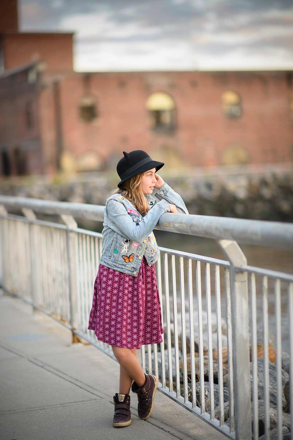 Young girl in a hat standing on waterfront in Brooklyn