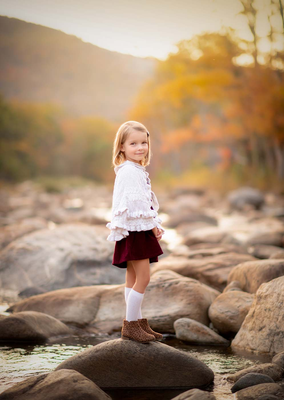 Girl standing on a rock near a river