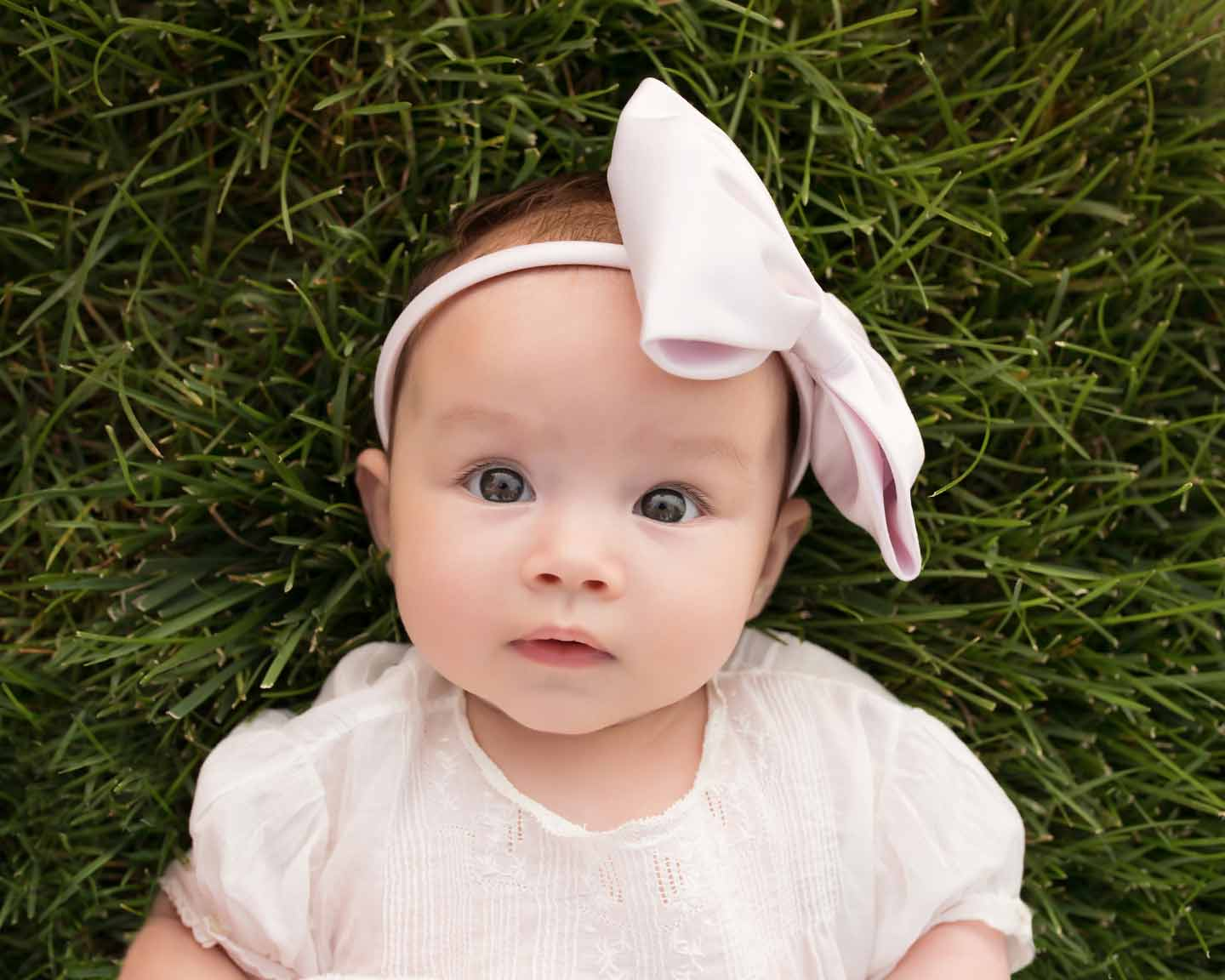 Baby girl with headband laying in grass