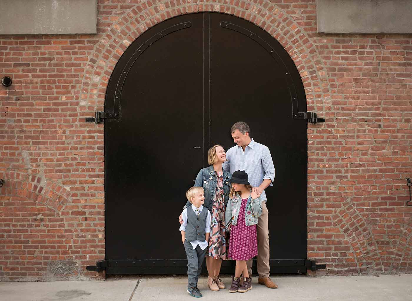 Modern NYC family standing near an iron gate in Brooklyn's industrial section