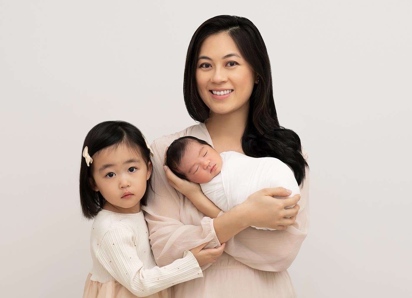 mother cradling newborn with big sister in neutral tones