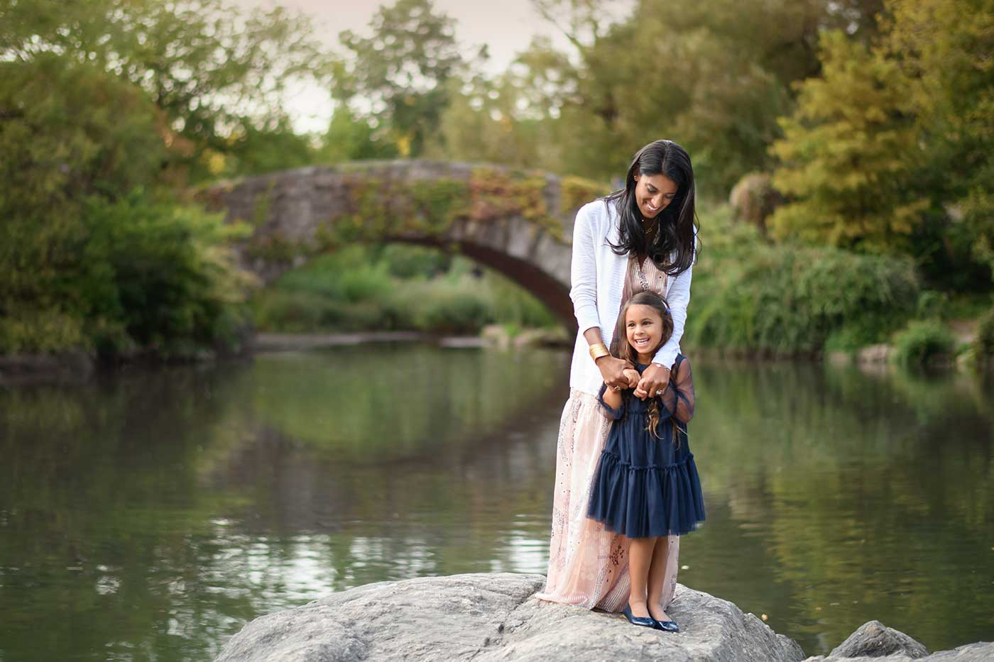 Mother posing with her daughter at a pond in Central Park