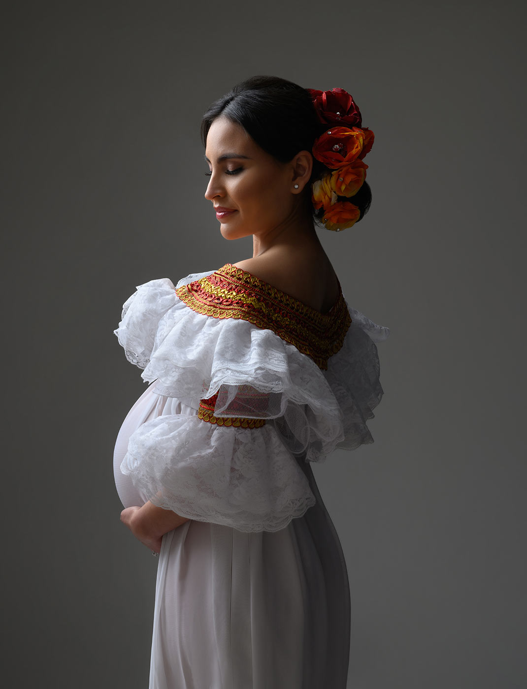maternity portrait with colorful flowers and traditional Spanish lace ruffle dress