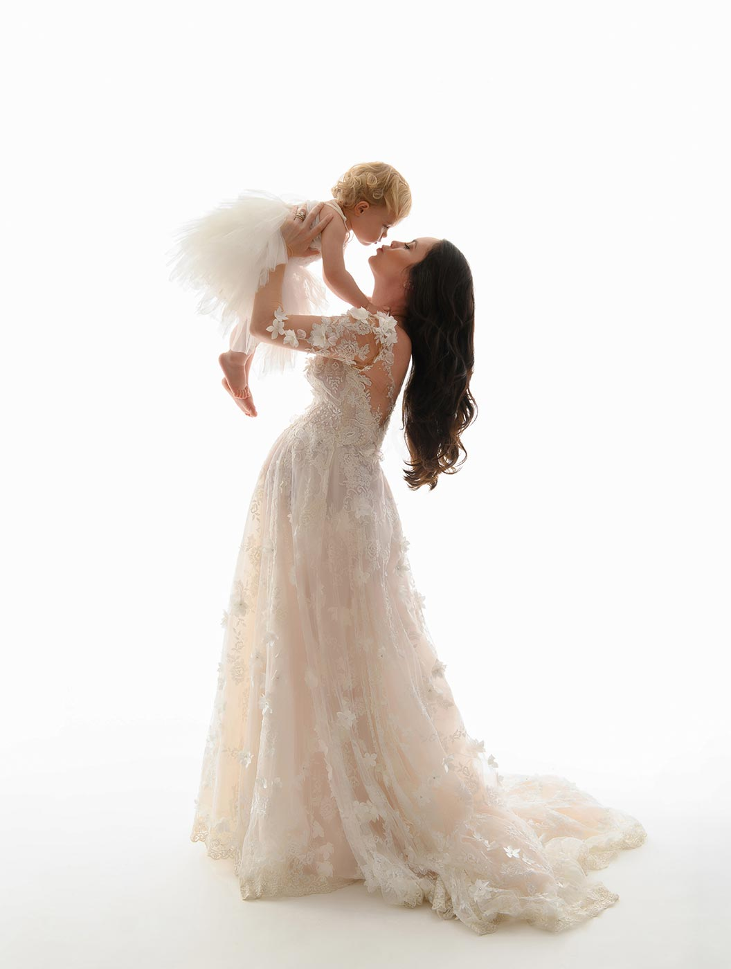 pregnant mother in white lace gown kissing baby with tutu dress nyc