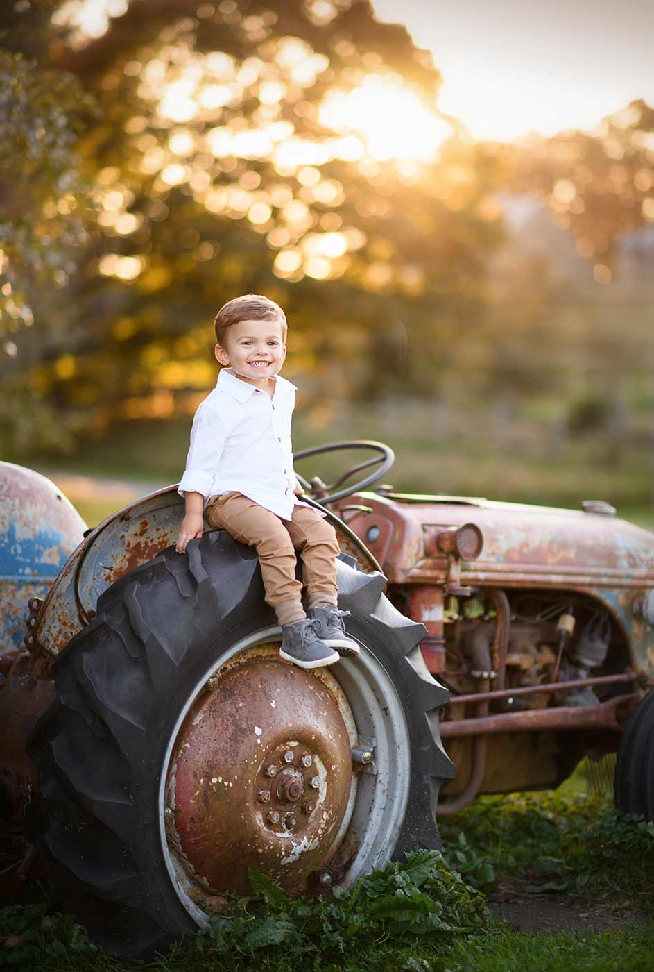 Boy sitting on a rusty tractor during sunset