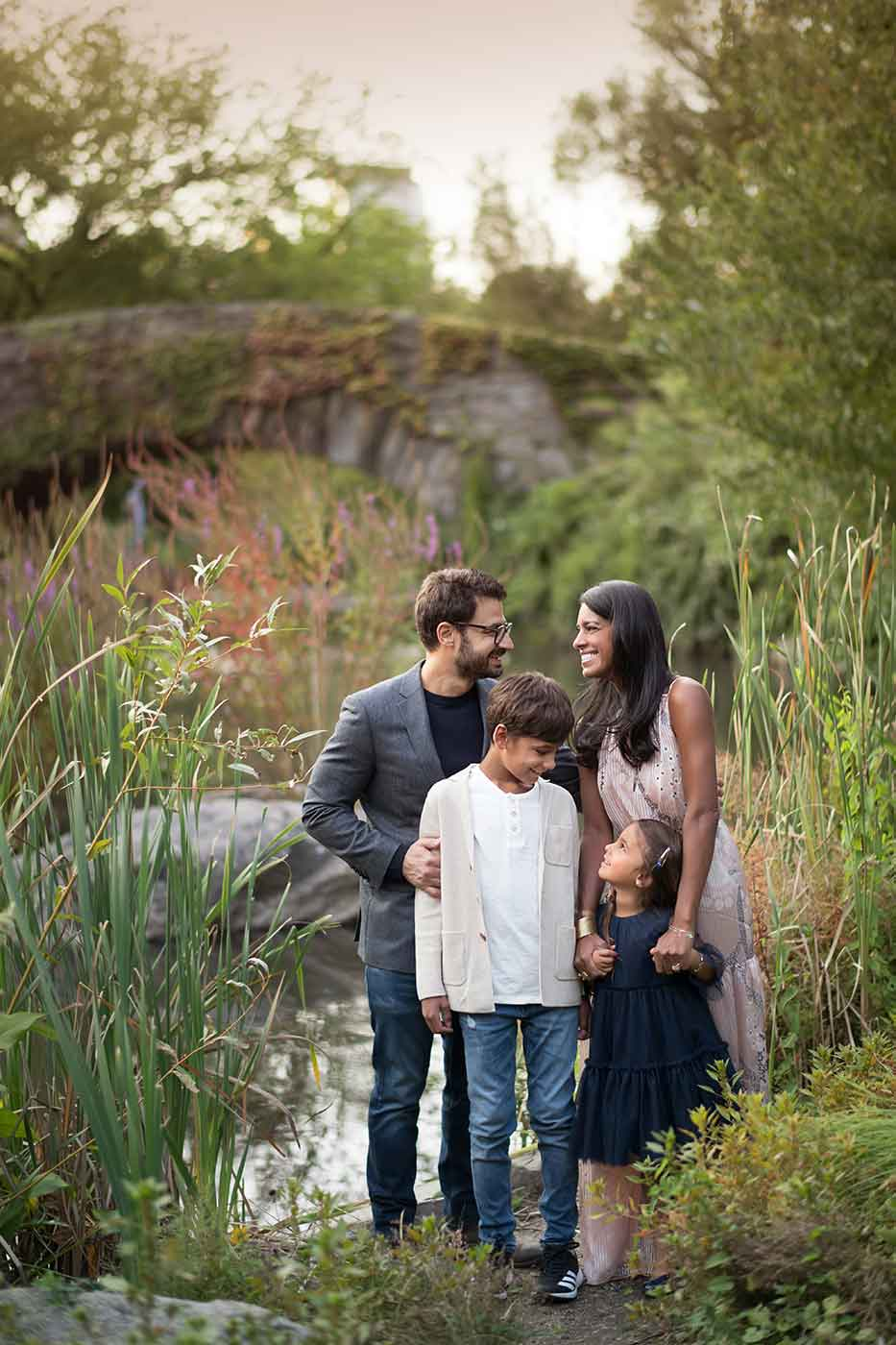 Family shares a happy laugh amongst tall grasses of Central Park