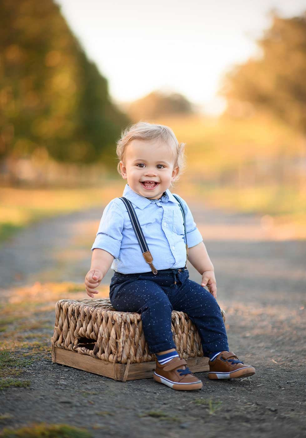 Happy toddler sitting on a basket at a farm and smiling