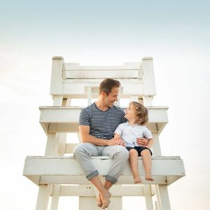 Father and son sitting on lifeguard tower in the Hamptons