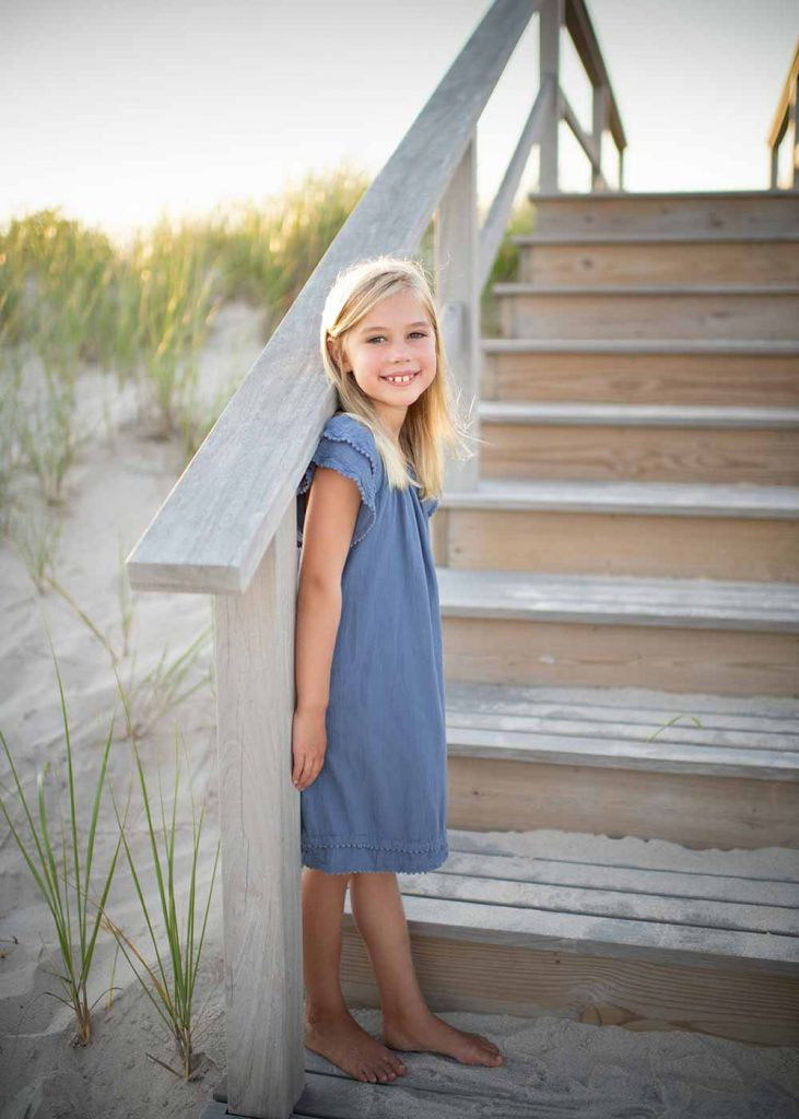 Young girl in a blue dress standing on a beach near Southampton NY