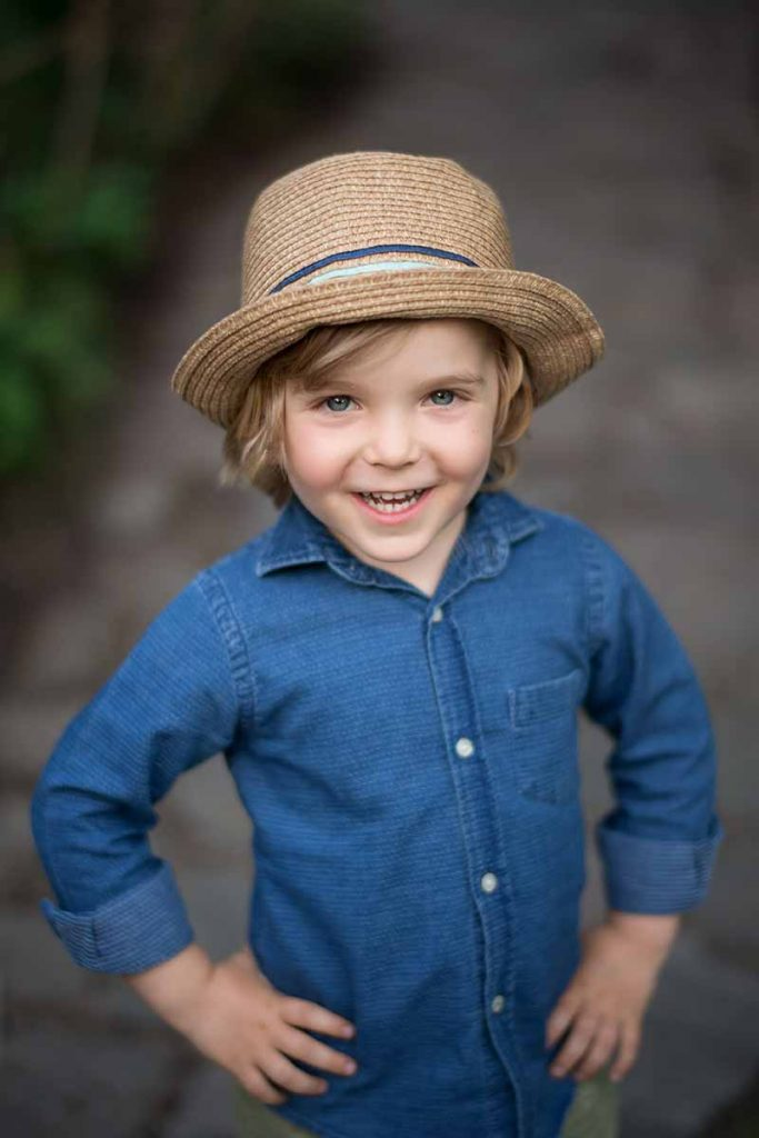 Young boy wearing a fedora smiling happily