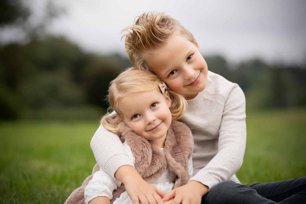 Brother hugging his little sister in a field