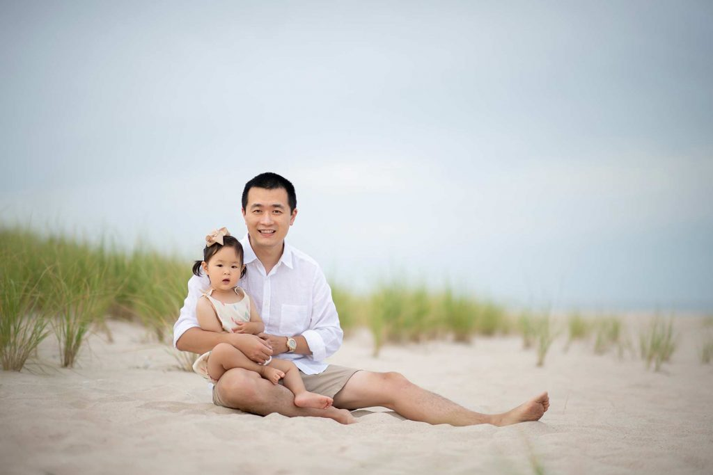 Happy father sitting with his daughter in sand near Amagansett, NY