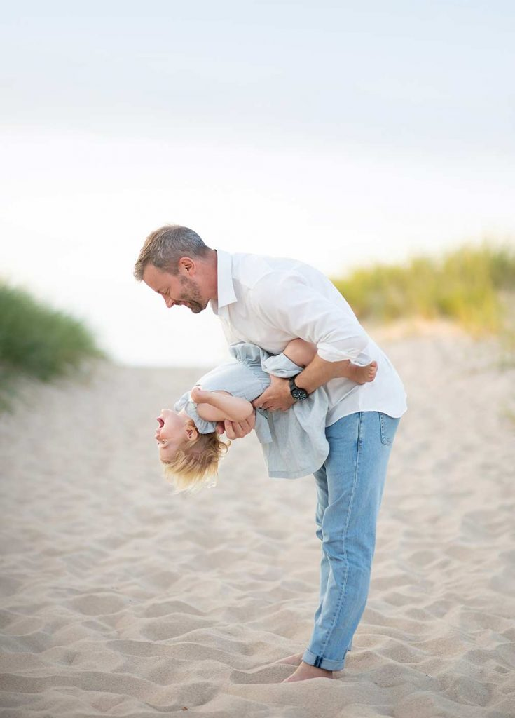 Father sharing a playful moment with his daughter on a beach near Westhampton, NY