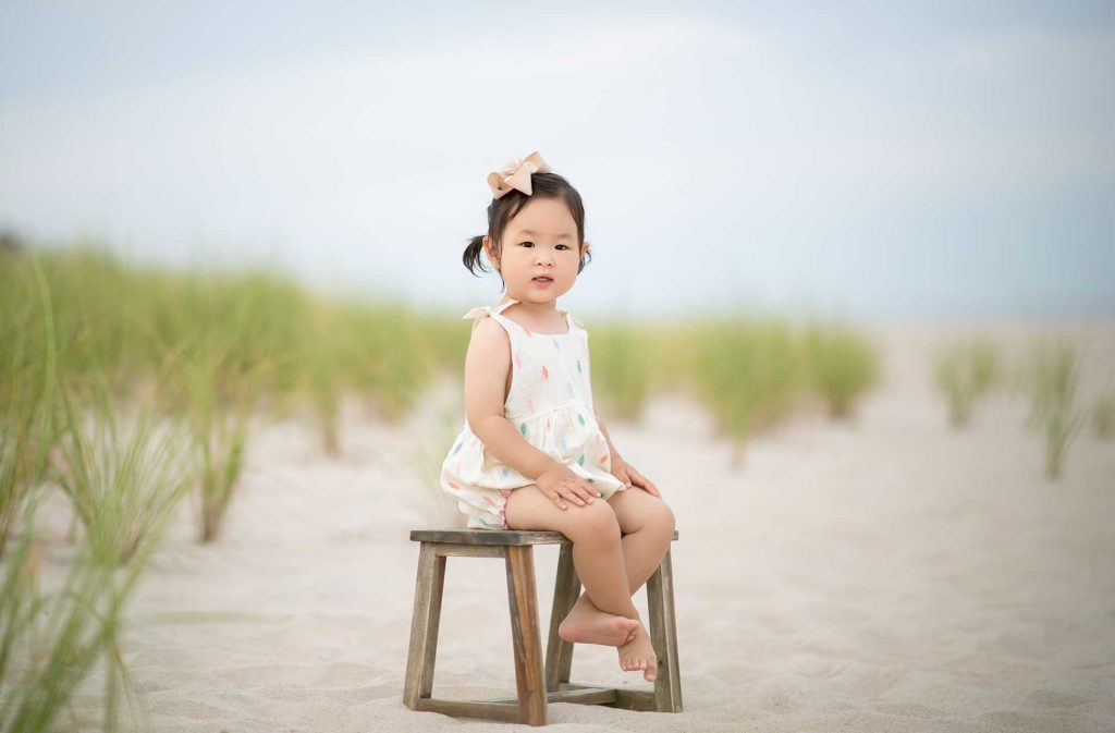 Toddler sitting on a sandy beach in East Hampton, NY