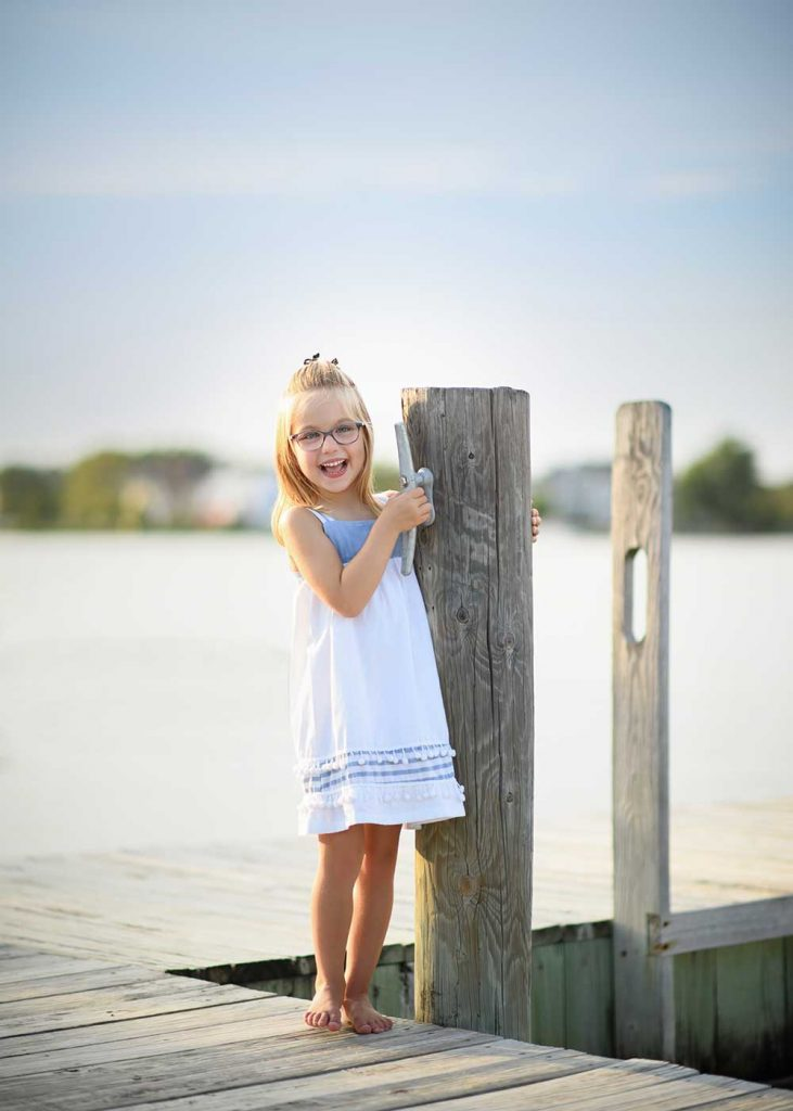 Girl on a dock smiling happily in Sag Harbor, NY