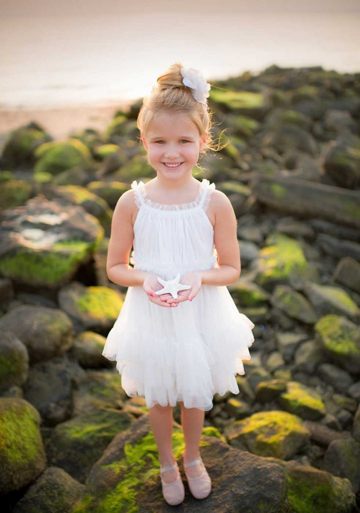 Youg girl in a white tutu holding a starfish on a beach