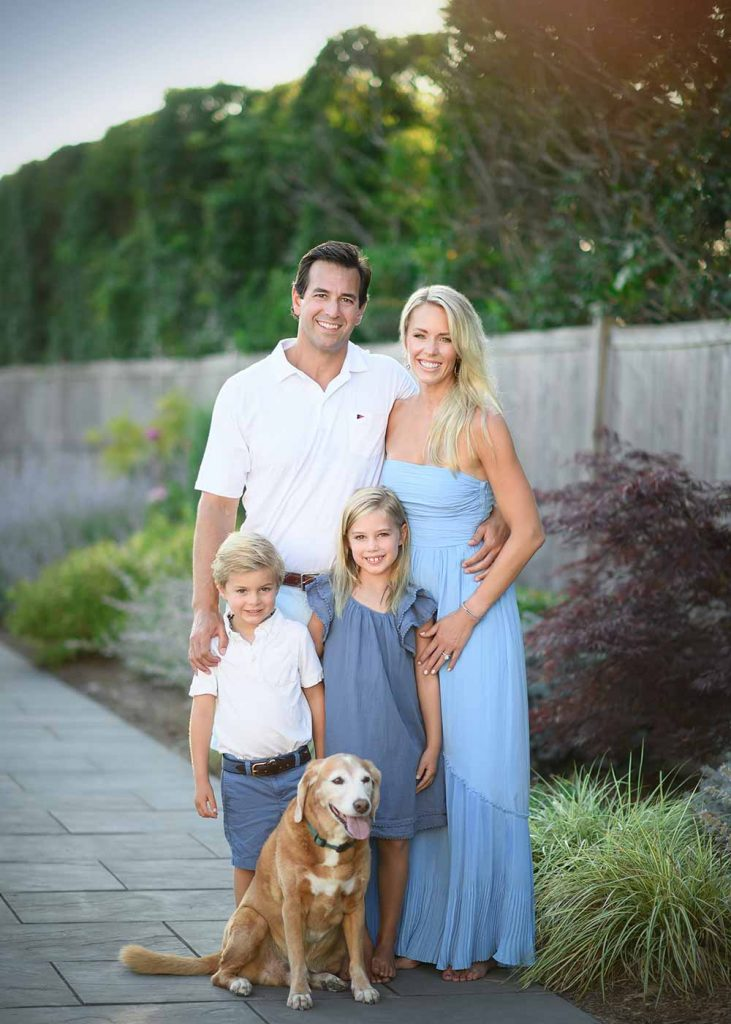 Stylish family posing for a portrait in their Southampton NY yard