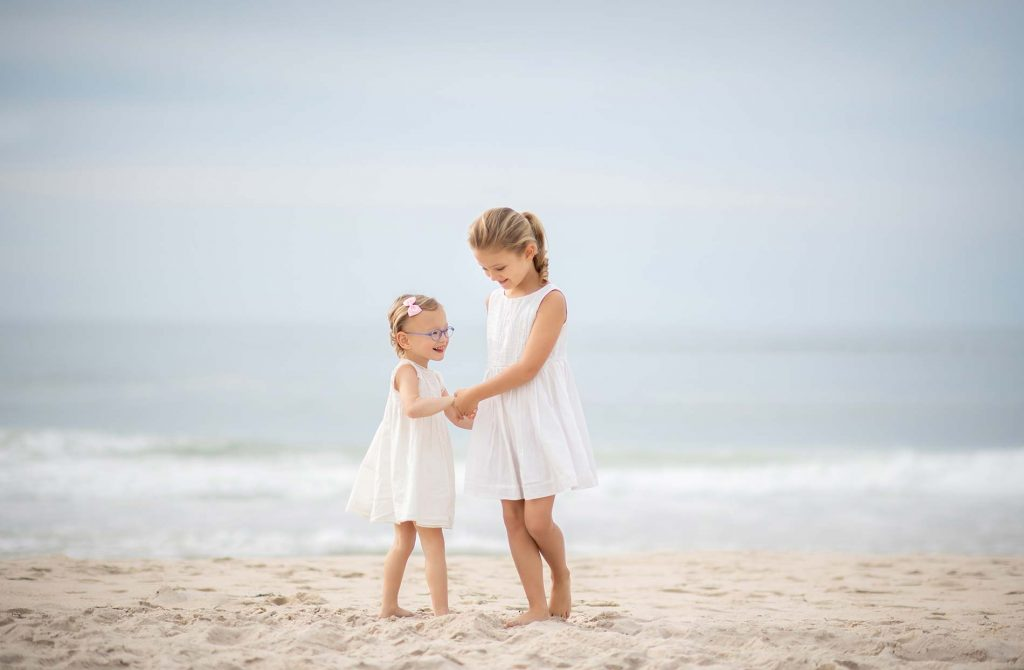 Two sisters in white dresses dancing on a beach in Southampton NY