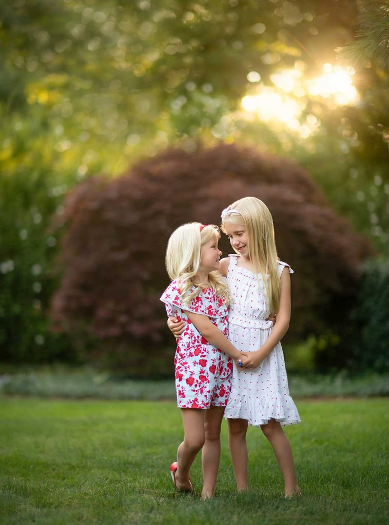 Two sisters holding hands in their Bridgehampton NY backyard