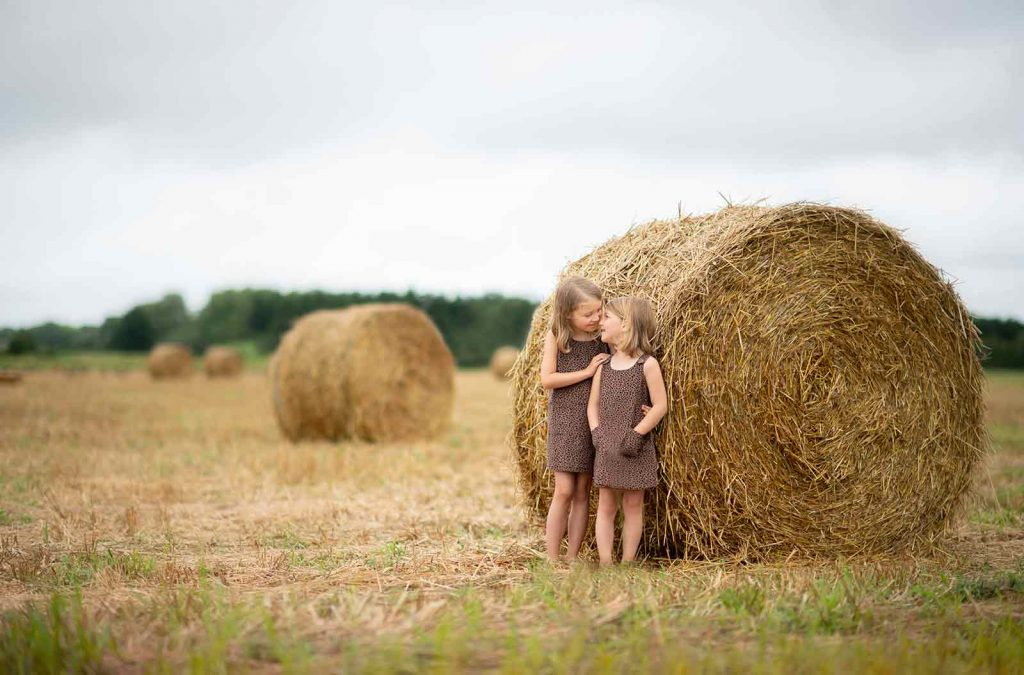 Sisters bonding on a farm in the Hamptons with rolled hay in the background