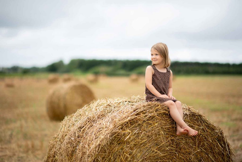 A girl sitting on rolled hay in East Hampton, NY