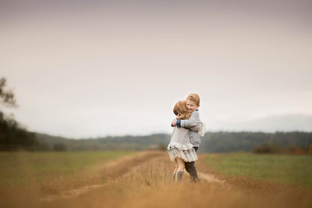 Brother and sister hugging each other on a farm road in Sag Harbor NY