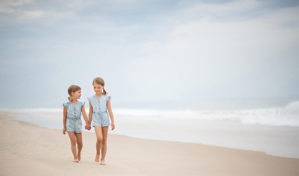 Two young girls holding hands on a beach