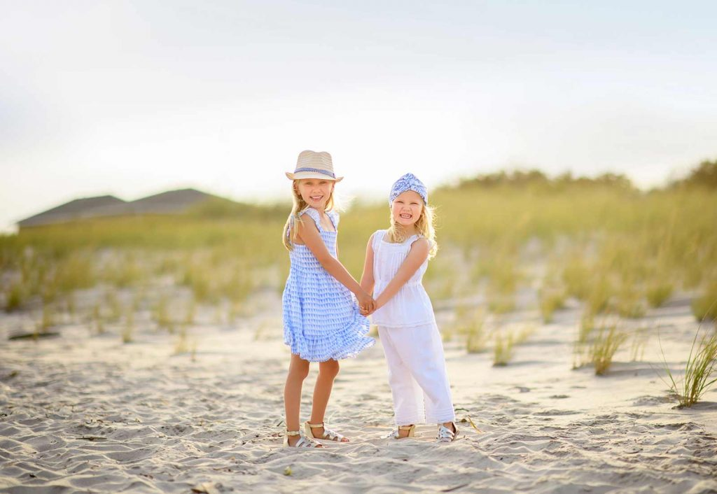 Two young sisters dancing in the sand at a beach in the Hamptons NY