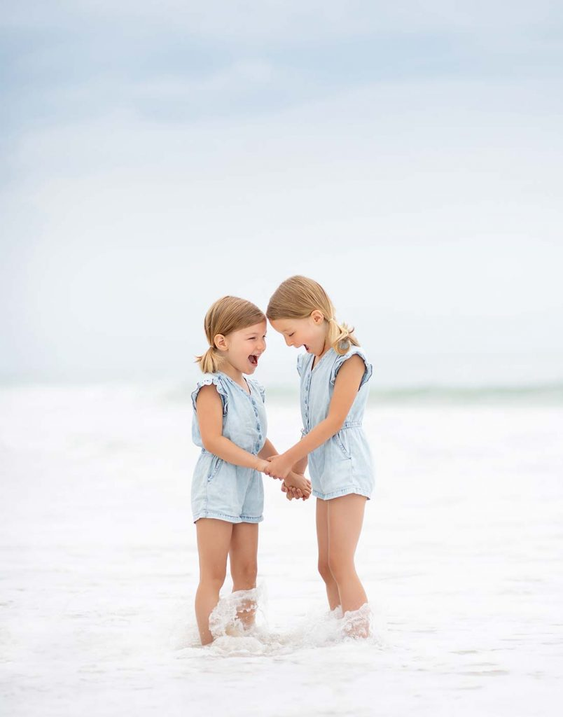 Two sisters in denim dresses sharing a laugh amidst the waves in East Hampton, NY