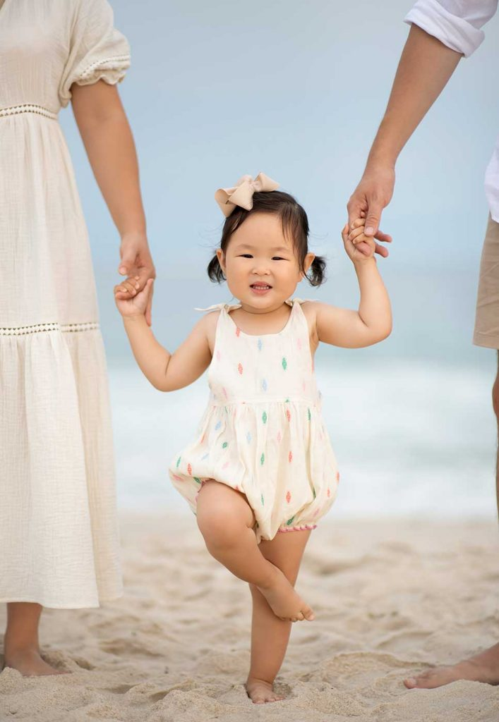 Happy girl with Mom and Dad standing in the sand