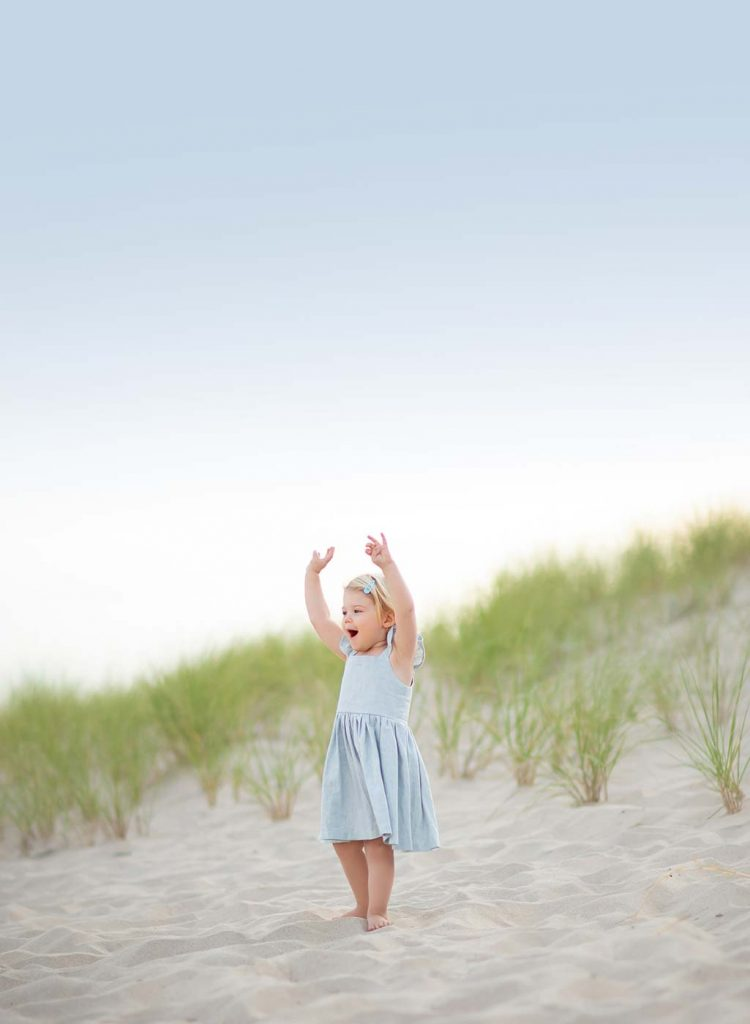 Young girl in a dress waving her hands at a beach in East Hampton NY